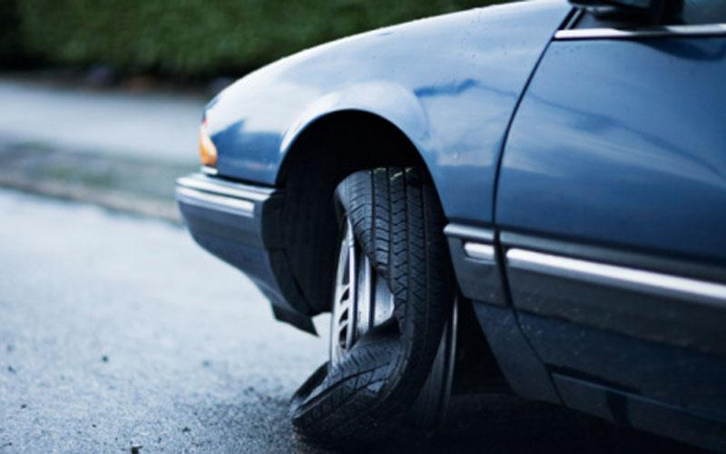 What's the best course of action if a tire blows at 100km/h on a passenger car?